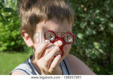 Young boy play with red fidget spinner in outdoors, focus on spinner.