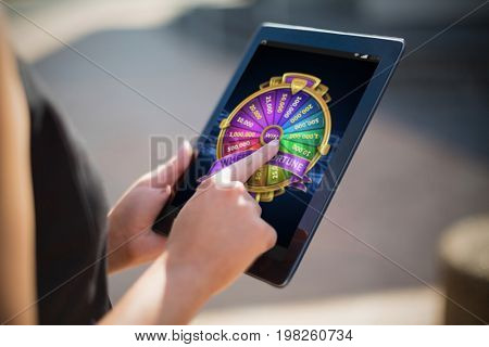 Colorful wheel of fortune on mobile display against businesswoman using digital tablet