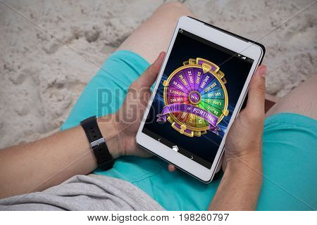 Colorful wheel of fortune on mobile display against man using digital tablet on the beach