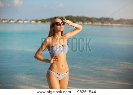 Spa wellness beach beauty woman relaxing and sun bathing near blue lagoon. Beautiful serene and peaceful young female model on holiday travel Maldives tropical resort. Sun tan cream protection concept
