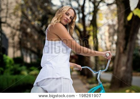 Digital composite image of blonde going on a bike ride against footpath by trees in city