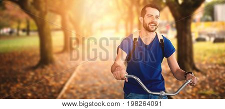 Young man riding bicycle against footpath amidst trees at park