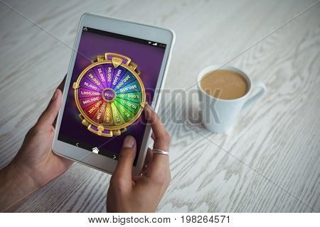 Multi colored fortune of wheel on mobile display against cropped hands of woman holding tablet at table