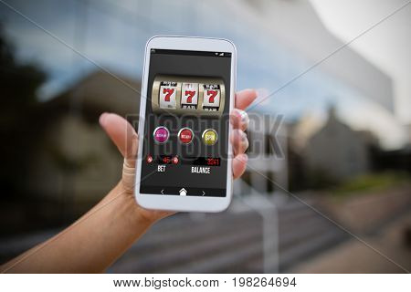 Casino slot machine app on mobile display against woman holding mobile phone