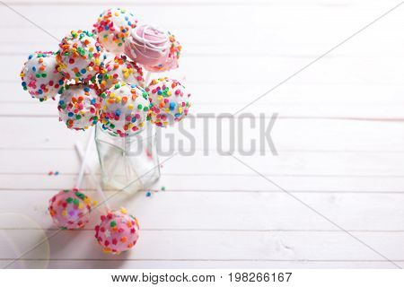 Colorful bright cake pops in jar on white wooden background. Selective focus. Place for text.