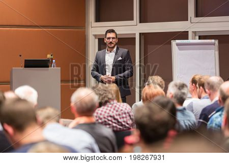 Speaker giving a talk at conference meeting business event. Audience at the conference hall. Business and Entrepreneurship concept.