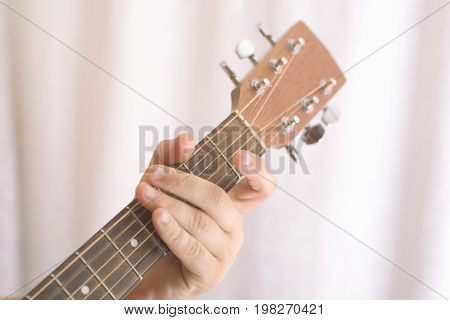 Photo of man's playing tuning guitar close-up