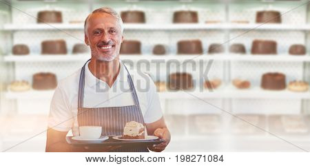 Portrait of male owner holding food and drink against desert case with delicious cakes
