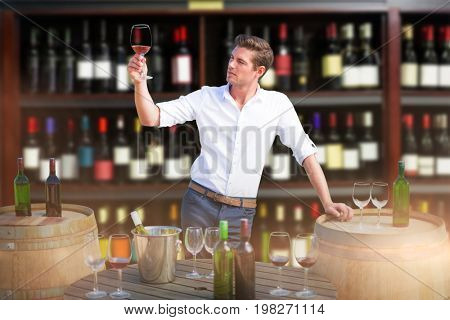 Young man holding red wine glass by barrels against wine bottles arranged on shelves