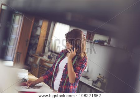 Young fashion designer working in her atelier having a phone conversation and taking orders for new models