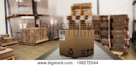 Packed parcel box on conveyor belt against many stack of cardboard boxes