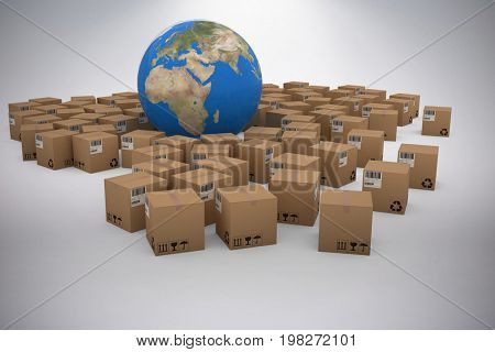 3D image of globe amidst cardboard boxes against grey background