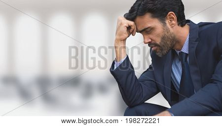 Digital composite of Worried business man sitting against office background