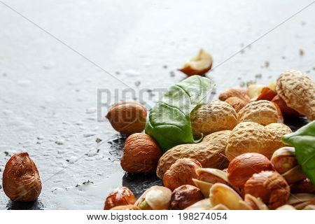 Basil leaves, fragrant pistachios and crunchy nuts on a light background. A glass full of light beer and salty snacks. Tasty appetizers for alcoholic beverages food or snacks. Copy space.