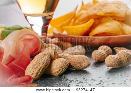A close-up picture of sliced prosciutto and peanuts on a gray blurred background. A cold alcohol beer on the table. Crunchy chips on a wooden plate. A big assortment tasteful snacks for beer.