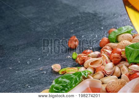 Basil leaves, fragrant pistachios and crunchy nuts on a gray background. A glass full of light beer and salty snacks. Tasty appetizers for alcoholic beverages food or snacks. Copy space.