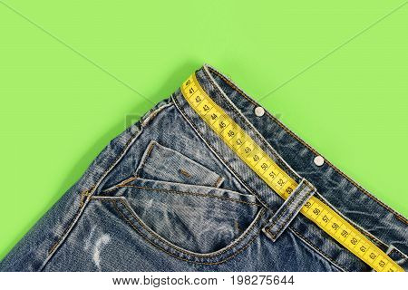 Top Part Of Denim Trousers Isolated On Green Background