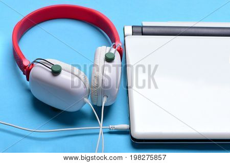 Headphones And Silver Laptop. Earphones In Red And White Colors