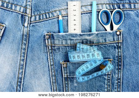 Tailoring And Design Concept: Tailors Tools In Jeans Back Pockets