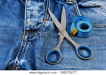 Making Clothes Concept: Metal Scissors And Measure Tape On Jeans