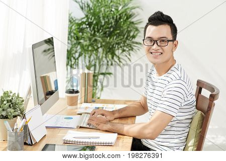 Portrait of cheerful Vietnamese businesman in casual clothes working on computer
