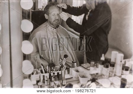 Old Sepia Photo Of Backstage Man Sitting In Front Of Mirror Getting Make-up.