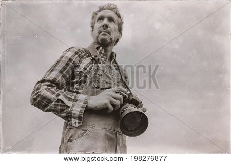 Old Sepia Photo Of Nature Photographer Outdoor On Overcast Day. Low Angle View.
