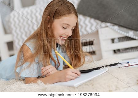 Adore learning something new. Charming young lady smiling while lying on the floor and holding a pencil while looking on a digital tablet and writing something in her notebook.