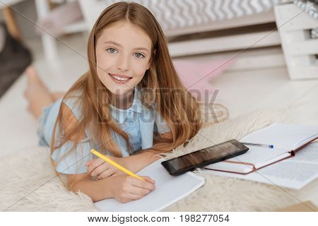 Intelligent generation. Grey eyed pretty child looking into the camera with a smile on her face while relaxing on the carpet and preparing her home assignment.
