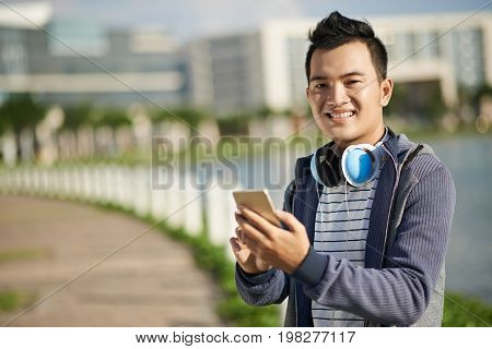 Happpy Vietnamese young man choosing track on his smartphone to listen to