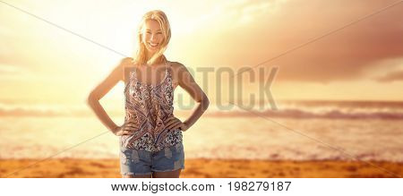 Happy woman with hands on her hips  against view of beach during sunset