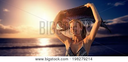 Smiling woman holding scarf in the air  against scenic view of sea against sky