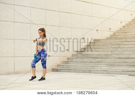 Young fit Asian woman checking smartphone and having some water during short break