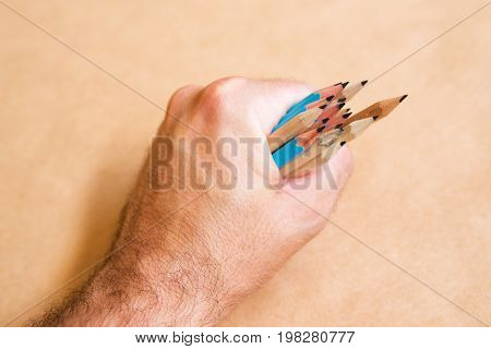 Male illustrator and sketch artist with handful of pencils selective focus