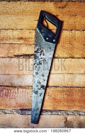The hand iron rusty saw hangs on a nail.Wood texture. background old panels.