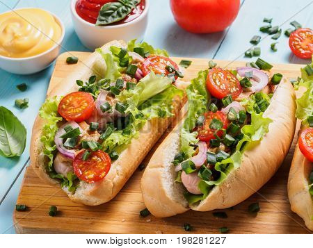 Close up view of homemade hotdogs with chicken, sausages, fresh vegetables, ketchup and mustard sauce on blue wooden background. Hot-dogs with tomatoes, onion, basil, letucce and spices.
