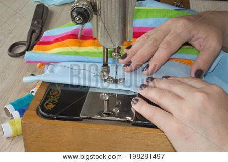 Sewing Process the sewing machine sew women's hands sewing machine. sewing machine and female scissors