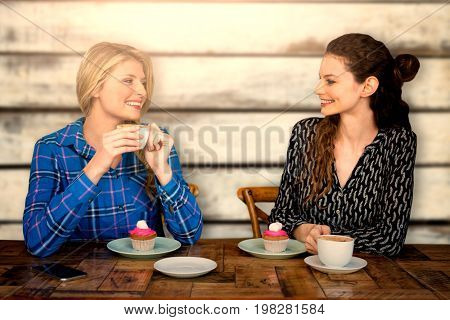 Women are having a coffee  against wood panels in row
