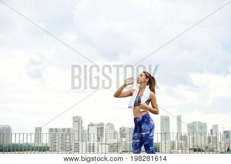 Fit young woman drinking water after training, big city is in the background