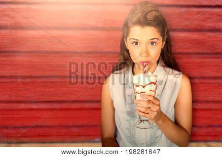 Young girl drinking milkshake against full frame shot of red wall