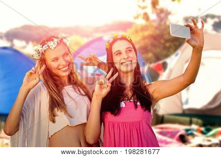 Smiling friends taking a selfie against empty campsite at music festival