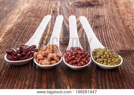 Various fresh legumes in spoons on wooden table
