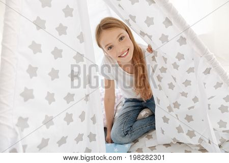 Peekaboo. Young lady of unearthly beauty peeping out from a tent while having fun and playing t home.