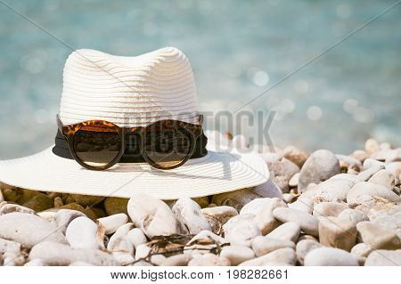 Summer compositions with woman's hat and sunglasses on the beach