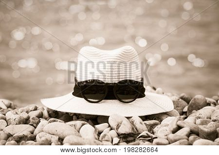 Summer compositions with woman's hat and sunglasses on the beach. Sepia effect