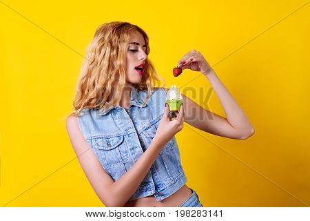 Attractive young woman trying to eat a cupcake with strawberry over the yellow background.