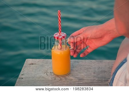 Close up of female hand holding glass bottle of fresh orange juice with drinking straw at the edge of wooden pier. Sea in the background. Summertime and healthy eating concepts.