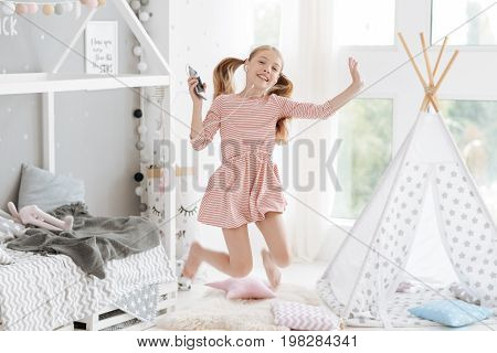 Jump with me. Radiant female youngster hoping as a bouncing ball and grinning widely while listening to the music playing on her smartphone in bedroom.