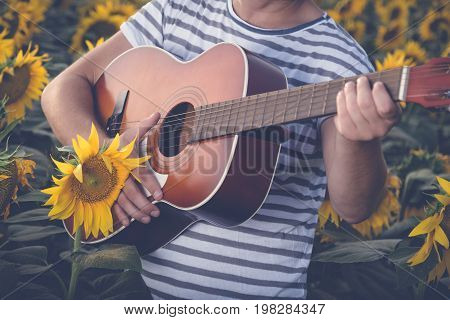 Close up of young modern guy playing acoustic guitar in sunflower field. Music and nature concepts.