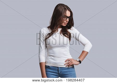 Always in style. Beautiful young woman in casual wear keeping eyes closed while standing against grey background